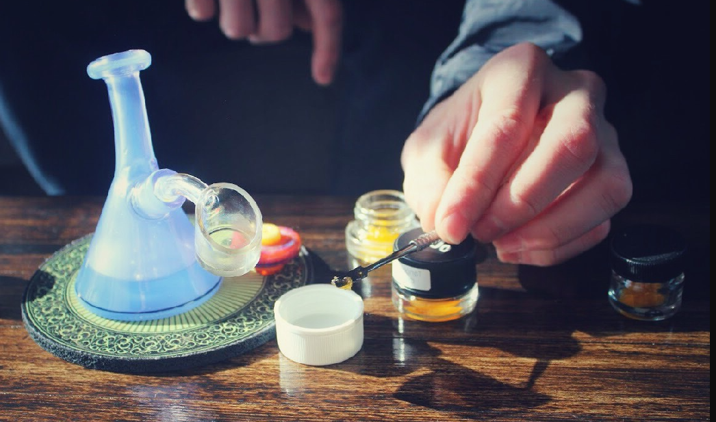 This image depicts a man about to put cbd concentrates into a bong